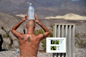 FILE PHOTO: Steve Krofchik of Las Vegas keeps cool with a bottle of ice on his head as the unofficial thermometer reads 130 degrees Fahrenheit (54.4 Celsius), with a mechanical fault on the display causing the numbers to render incorrectly, at the Furnace Creek Visitors Center in Death Valley, California, U.S. August 17, 2020. REUTERS/David Becker/File Photo
